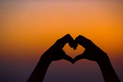 Silhouette of heart made hands at sunset Stock Photo