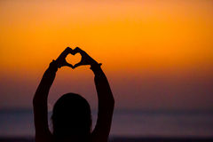 Silhouette of heart made hands at sunset Royalty Free Stock Photo