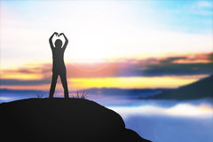 Silhouette heart shape made with a girl arm over sunset Stock Photography