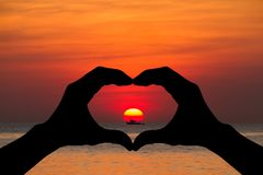 Silhouette heart shaped hands gesturing on blurred sunset over the beach. Love concept Royalty Free Stock Photos