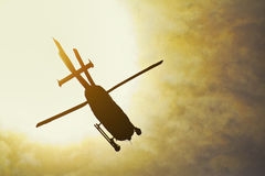 Silhouette of a helicopter flying in the rays of the setting sun Royalty Free Stock Photography