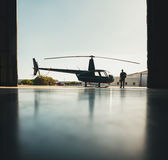 Silhouette of helicopter and a pilot in hangar Stock Images