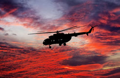 Silhouette of helicopter on sunset sky. Stock Images