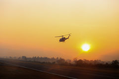 Silhouette helicopter take off from Mae Sot airport runway in w. Estern border of Thailand with fog and forest background at sunrise stock photos
