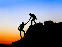 Silhouette of helping. Hand between two climber Royalty Free Stock Photos