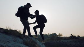 Silhouette of helping hand between two climber. Two hikers on top of the mountain, a man helps a man to climb a sheer stock video