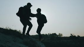 Silhouette of helping hand between two climber. two hikers on top of the mountain, a man helps a man to climb a sheer stock footage