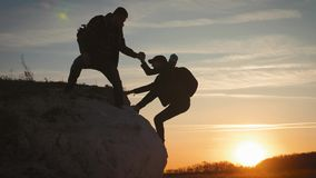 Silhouette of helping hand between two climber. two hikers on top of the mountain, a man helps a woman to climb a sheer