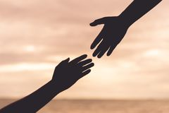 Silhouette helping hands on blurred sea and sky background. Friendship Day concept royalty free stock photography