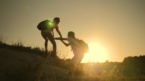 Teamwork. Silhouette of children holding out a helping hand. Two boys tourists on top of the mountain. Children help. Silhouette of helping hands between two stock footage