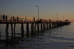 Silhouette of Henley Beach pier at dusk in Adelaide South Australia. Silhouette of people walking on Henley Beach pier at dusk. Henley Beach pier is a very stock image
