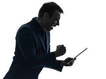Silhouette heureuse de succès de comprimé numérique d'homme d'affaires Images stock
