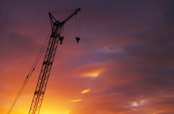 Silhouette of high crane with two hooks on sunset sky. Silhouette of high crane with two hooks on fiery sunset sky background Royalty Free Stock Images