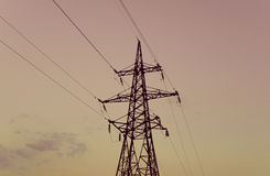 Silhouette of high metal electricity tower with wire. Sunset tim Royalty Free Stock Images