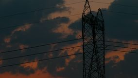 Silhouette of High voltage electric pylon, tower in sunset, time lapse of clouds moving behind the pylon, 4k UHD