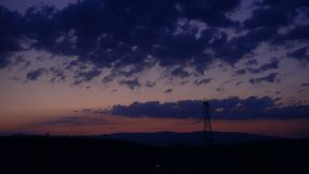 Silhouette of High voltage electric pylon, tower in sunset, time lapse