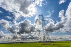 Silhouette of the high voltage electric pylon towers on the background of beautiful clouds royalty free stock photography