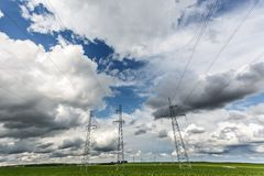 Silhouette of the high voltage electric pylon towers on the background of beautiful clouds stock image