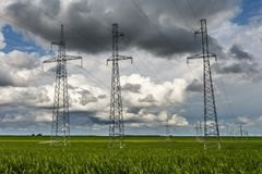 Silhouette of the high voltage electric pylon towers on the background of beautiful clouds royalty free stock photos