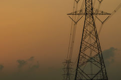 Silhouette of high voltage electric tower. With sunset background Stock Photography