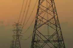 Silhouette of high voltage electric tower. With sunset background Stock Images