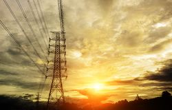 Silhouette High voltage electric tower. On sunset time and sky on sunset time background Royalty Free Stock Image
