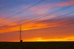 Silhouette of high voltage electrical pole structure. At sunset Royalty Free Stock Images