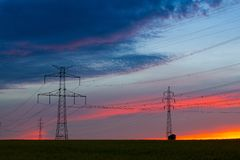 Silhouette of high voltage electrical pole structure. At sunset Stock Photo
