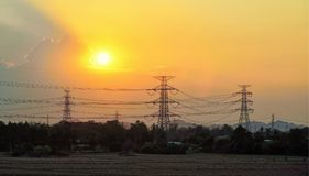 Silhouette of high voltage electrical pole structure. At sunset Stock Photography