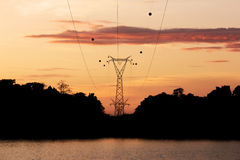 Silhouette high voltage post, power transmission tower at Sirindhorn Dam in the morning time stock photos