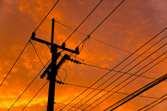 Silhouette of high voltage power lines against orange colorful sky Royalty Free Stock Photo