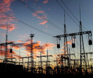 Silhouette of High voltage power plant and transformation station at sunset. Stock Photos