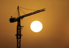 Silhouette of highrise crane during sunrise Stock Images