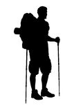 A silhouette of a hiker with backpack. A silhouette of a full length portrait of a hiker with backpack holding hiking poles isolated on white background Stock Photos