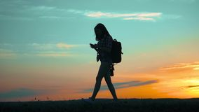 Silhouette hiker girl traveler with smartphone navigation search ways. the girl nature search position navigation slow. Silhouette hiker girl traveler with stock footage