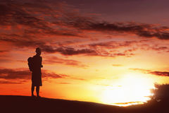 Silhouette hiker man with backpack standing enjoying sunset Stock Photography