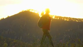 Silhouette of hiker tourist woman with backpack trekking on mountain at sunset. Hiker girl, Female traveler woman. Silhouette of hiker tourist woman with stock footage
