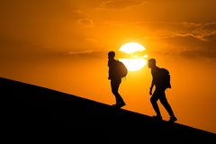 Silhouette of hikers,people side view walking toward successful .Travel and success concept. Silhouette of hikers,people side view walking toward successful.Two Royalty Free Stock Images
