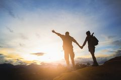 Silhouette of hikers standing on top of hill and enjoying sunrise over the valley royalty free stock image