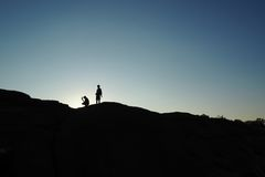 Silhouette of hikers at sunset Stock Photo