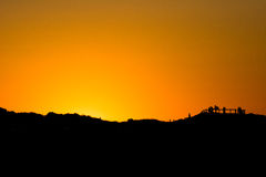 Silhouette hill at sunset at Outback Western Australia. Silhouette hill at sunset, Sun at dark orange sunset shining over lines of forested mountain receding Stock Photography