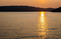 Silhouette of hills against water reflecting sunset Stock Photos
