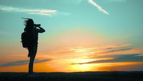 Silhouette Hipster hiker silhouette girl is shooting video of beautiful nature sundown on cell telephone smartphone slow. Silhouette Hipster hiker silhouette stock video