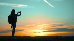 Silhouette Hipster hiker silhouette girl is shooting video of beautiful nature sundown on cell telephone smartphone slow. Motion video. Female tourist taking stock footage