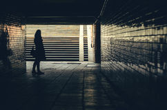 Silhouette of hipster woman in tunnel. Silhouette of women against underground passage stairs leading up on the street stock photos