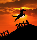 Silhouette horse jumping over 2014. Silhouette of horse jumping over 2014 number to embrace the new year Stock Photography