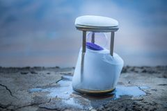 Silhouette hourglass is disintegrating on hand Pocket watch at last sunlight (Concept of wasting time. A concept of frozen time. Hourglass in ice. Creative royalty free stock photos