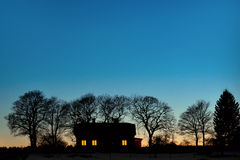 Silhouette of house. With bare trees on dark blue sky in evening Stock Photo