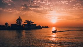 Silhouette of House and Trees by Water during Golden Hour Stock Images