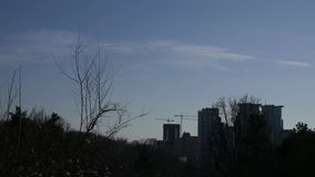 Silhouette of houses under construction and cranes against the blue sky stock video